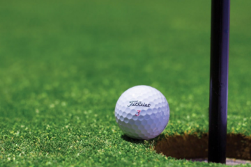 pallina da golf accanto a buca